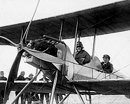 Two men in flying gear seated in tandem open cockpits of a biplane with a four-bladed propeller