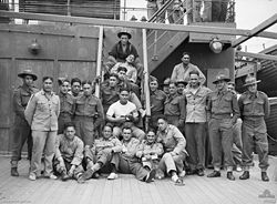 A group of men standing or lying on the deck of a ship, posing for the camera
