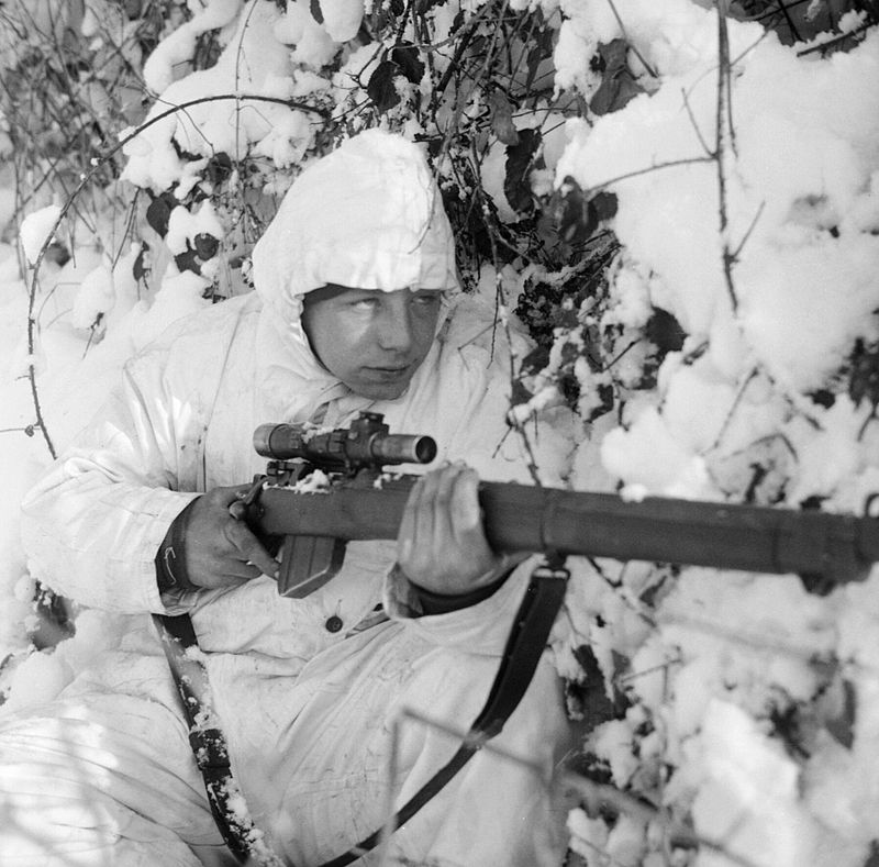 A 6th Airborne Division sniper on patrol in the Ardennes, wearing a snow camouflage suit, 14 January 1945. B13676.jpg