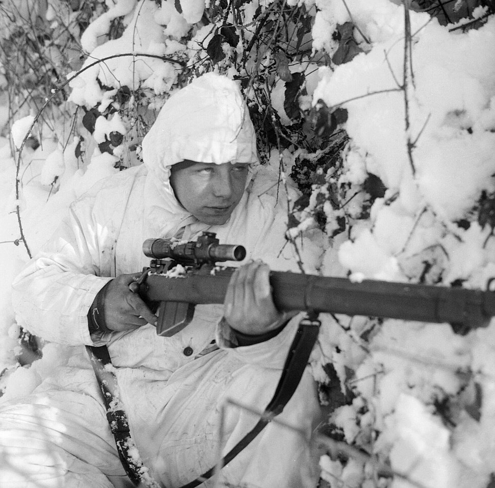 A 6th Airborne Division sniper on patrol in the Ardennes, wearing a snow camouflage suit, 14 January 1945. B13676