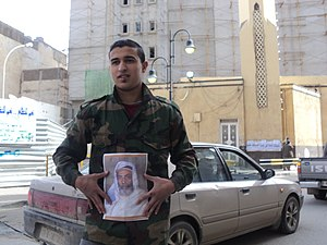 Timeline of the 2011 Libyan Civil War before military intervention - A young Libyan carrying King Idris's photograph during a protest in Benghazi on 23 February 2011.
