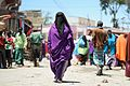 A Somali woman walks down the street in Mogadishu's Hamar Weyne market on October 3. Ahead of Eid al-Adha, which begins this evening, many of Mogadishu's residents have been out preparing for the (15404528826).jpg