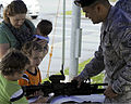 A U.S. Airman with the 18th Security Forces Squadron talks to family members about the M4 carbine with an M203 grenade launcher attached during the open house portion of National Police Week at Kadena Air Base 130515-F-FL836-186.jpg