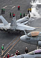 A U.S. Marine Corps F-A-18C Hornet aircraft assigned to Marine Fighter Attack Squadron (VMFA) 323 prepares for launch from the flight deck of the aircraft carrier USS Nimitz (CVN 68) June 13, 2013, while 130613-N-LP801-086.jpg