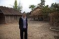 A grandmother stands in front of the family house (10662225203).jpg