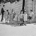 Acht chique aangeklede kinderen op een rij, vergezeld van een oude vrouw, Bestanddeelnr 255-3287.jpg