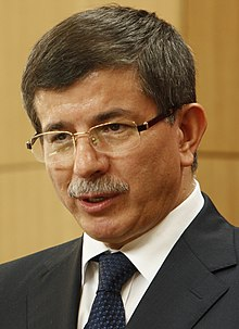 Ahmet Davutoğlu answering questions from the media in London, 8 July 2010 (4774547672) (cropped).jpg