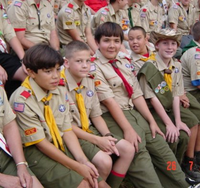 American Boy Scouts sitting around a campfire ring at a week long summer camp.png