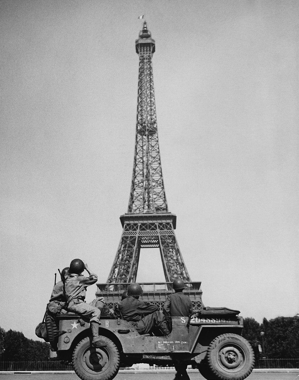 American soldiers watch as the Tricolor flies from the Eiffel Tower again