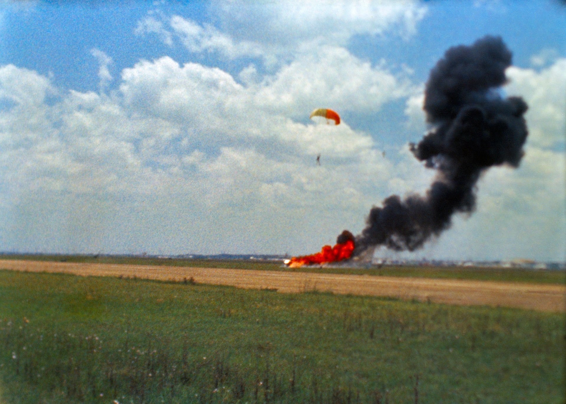 An indistinct photo of a smoke trail rising from an area of orange fire in a recently harvested field. A white and orange parachute is recovering a human figure above and to the right of the fire.