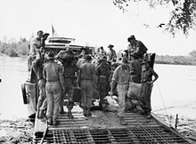 Soldiers disembark from a landing craft