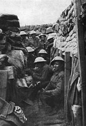 Black and white photo of a group of men wearing military uniform, including helmets, in a trench. Four men are crouching on the floor of the trench and another four are standing.