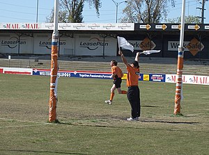 Umpire (Australian rules football) - A goal umpire signalling a goal with two white flags, and a Boundary umpire.