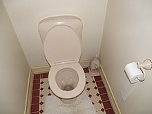 A Small Room With Flush Toilet Brush Hidden In Decorative Holder And Roll For Paper Can Be Seen To The Right Of