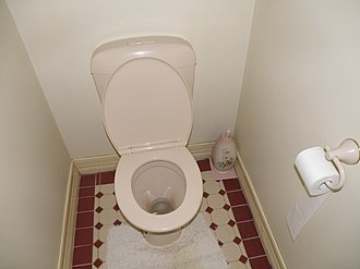 Toilet (room) - A small room with a flush toilet. A toilet brush (hidden in a decorative holder) and a toilet roll holder for toilet paper can be seen to the right of the flush toilet.