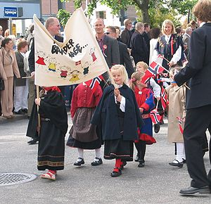 Norwegian Constitution Day - The kindergarten part of a Children's parade. The Gákti, the traditional clothing of the Sami people, is used by one of the small children.