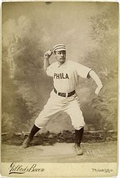 A baseball player is posing as if in the action of throwing a baseball.