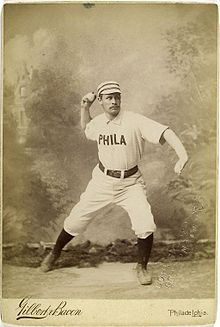 A sepia-toned baseball card image of a man wearing an old-style white baseball uniform and striped pillbox cap