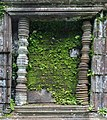 Blind window with moss-covered stones in the ruined Khmer Hindu temple complex of Wat Phou, Champasak, Laos.jpg