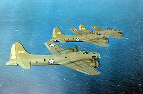 Three olive green four-engined propeller aircraft fly over the ocean.