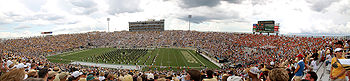A football stadium from the upper portion of the seats with several rows of people dressed in black on the field.