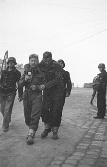 two British soldiers one wounded being escorted by three armed Germans