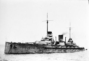 A large, light gray warship sits in harbor, the two forward gun barrels are turned slightly to the left.