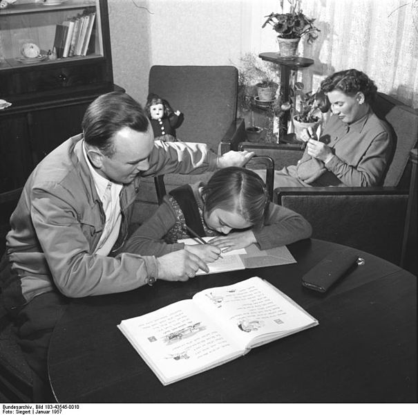 A black-and-white, vintage photo of a father helping his child with their homework. In the background, mother knits in her sitting chair.
