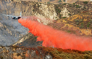Phos-Chek - C-130E Hercules equipped with a Modular Airborne FireFighting System makes a Phos-Chek fire retardant drop in Southern California in October 2003.