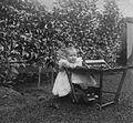 COLLECTIE TROPENMUSEUM De baby van de familie Van Schouwenburg in een verrijdbare kinderstoel in de tuin TMnr 60024439.jpg