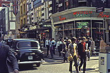Colour photo of a busy city intersection with two young white males walking across in the foreground