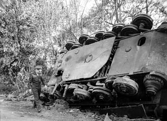 Tiger II - SHAEF commander Gen. Eisenhower walks by an overturned Tiger II; note the overlapping, non-interleaved steel-rim roadwheel arrangement