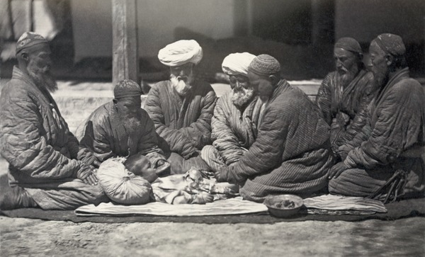 Men seated on the ground near a small boy who is being circumcised, Central Asia