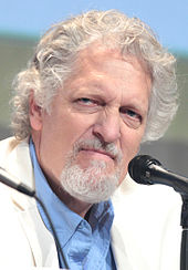 A white man with a short white beard, and white and grey curly hair. He wears a white suit with a blue shirt. The man stares away from the camera looking angry.