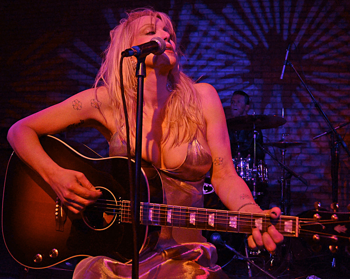 Woman in dress playing acoustic guitar and signing in microphone