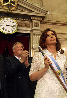Cristina Fernández de Kirchner in formal presidential attire, including the presidential scepter. Husband and former president Néstor Kirchner stands behind her.