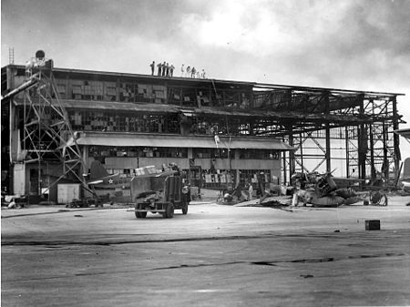 A large structure with most of the steel supports visible. Other materials that form the structure are burned, destroying, and hanging off the steel. A fire truck sits parked in front.