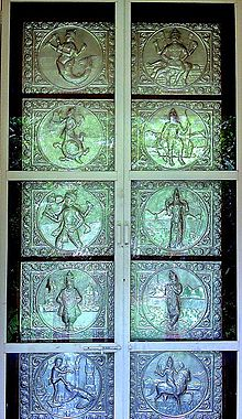A silver door with ten panels in two columns. The panels depict from top left clockwise a lion-faced man, a man with a bow and axe, a man with a bow, a man playing a flute, a man on a horse, a man with one of his feet on the head of a kneeling man, an arms-akimbo man, a boar-faced man, a man whose body below the waist is a tortoise and a man whose body below the waist is a fish.