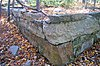 An angular stone retaining wall with dead leaves in a forest