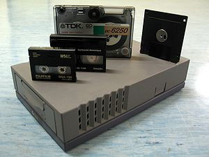 "Tape drive - DDS tape drive. Above, from left  to right: DDS-4 tape (20 GB), 112m Data8 tape (2.5 GB), QIC DC-6250 tape (250 MB), and a 3.5"" floppy disk (1.44 MB)"