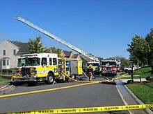 A photograph of a street in Ashburn, with a fire engine and fire fighters in teh foreground