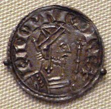 A coin depicting a bearded man facing to the right holding a sceptre, with a Latin inscription going from left to right over him