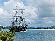 A three-masted sailing ship crossing a bay
