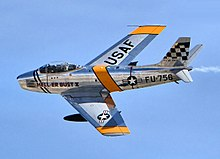 Photographie couleur d'un avion North American F-86 Sabre en vol se détachant sur un ciel bleu.