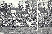 Photo noir et blanc d'un but marqué dans le petit filet, hors de portée du gardien lors d'un match de football.