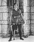 Fairbanks Robin Hood standing by wall w sword.jpg