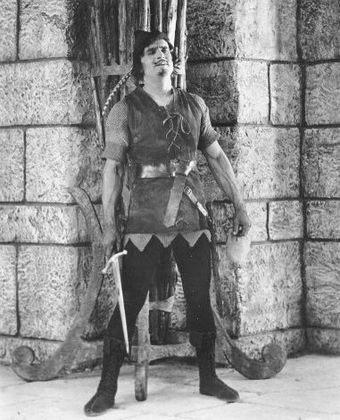 Douglas Fairbanks as Robin Hood Fairbanks Robin Hood standing by wall w sword.jpg
