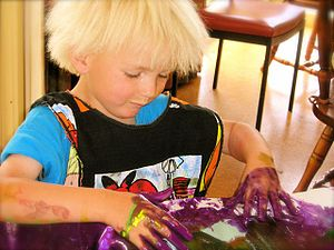 a child painting a piece of paper using hands and fingers