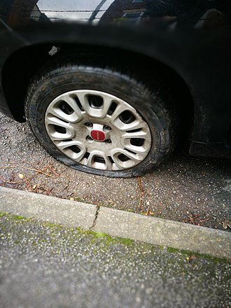 Flat tire - A flat tire on an automobile.