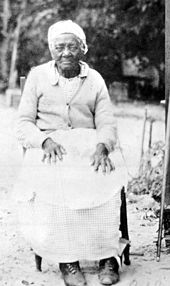 Black and white photo of an elderly African American woman looking at the viewer, wearing turn of the 20th century work clothes, a do-rag, and seated with her hands on her knees